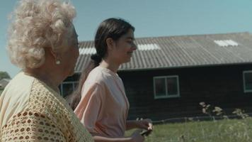 Woman and girl walking and talking in countryside video