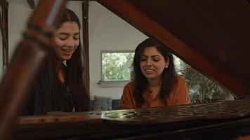 Girl and woman sitting at grand piano whilst playing and talking video
