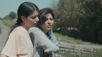Woman and annoyed girl talking and leaning on fence in the countryside video