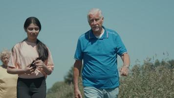 A man a girl and a woman walking and talking in the countryside video