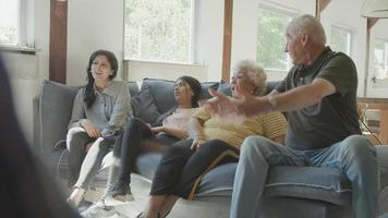 Two women a man and a girl sitting on sofa discussing whilst watching television video