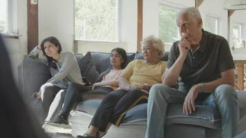 Two women a man and a girl sitting on sofa watching something exciting on television video