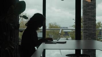 Mujer escribiendo en la computadora portátil y respondiendo llamadas telefónicas video