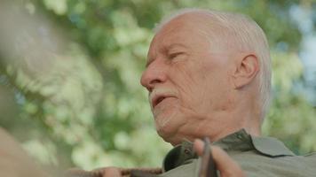 homme assis dans le jardin parle vivement video