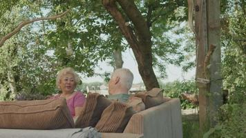 Woman and man sitting on couch in garden having vivid conversation video