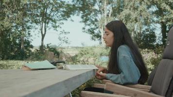 flicka sitter vid bordet i trädgården gör läxor läser högt video