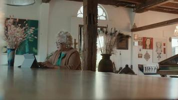 Woman sits at table typing on laptop video