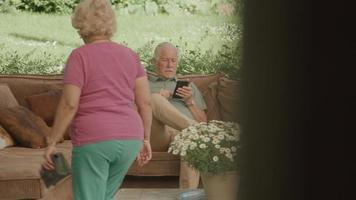 femme avec pochette rejoint l'homme assis sur un canapé dans le jardin à la fois holding smartphones video