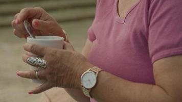 Femme assise dans le jardin s'agite dans la tasse et sirote tout en parlant video