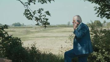 Hombre de pie en el jardín con vista al campo terminando la llamada telefónica video