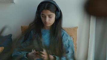 Girl with headphone sitting in corner whilst typing on smartphone video