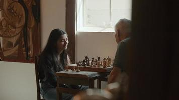 Girl and man playing chess at table video