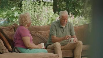 Woman and man sitting on couch in garden having serious conversation video