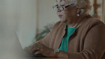 Woman sits at table using laptop and talks video