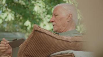 Man sitting in garden using tablet whilst talking video