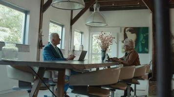 Woman and man sitting at table having conversation and both using laptops video