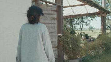 Woman walks in yard with book and pushes garden door video