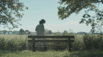 femme s'assoit sur un banc en bois dans le pays et commence à lire un livre video