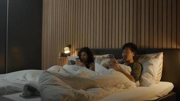 Woman reads and man looks at smartphone whilst lying in bed video