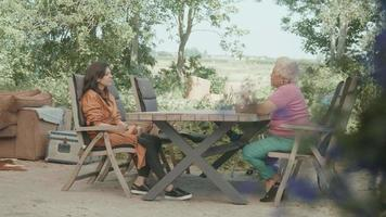 Two women having conversation sitting at table in garden video
