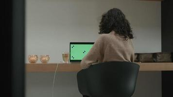 Woman at table has video call on laptop with green screen and drinks