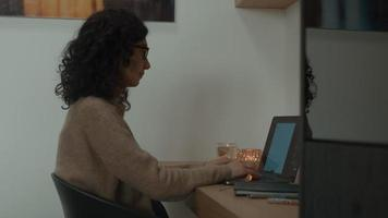 Woman at table typing on laptop video