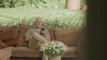 Man sitting on couch in garden looking at smartphone video