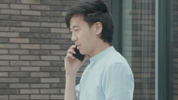 homme debout à l'extérieur de parler sérieusement sur smartphone video