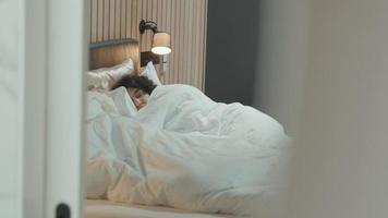 Woman awakes and gets up whilst man still sleeps video
