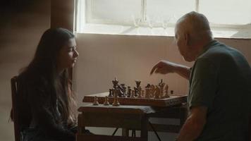 menina e homem jogando xadrez enquanto o homem fala e aponta para as peças de xadrez video