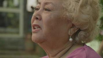 Woman sitting in garden talks vividly video