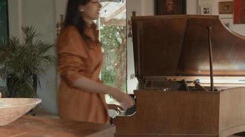 une fille joue du piano et une femme s'assoit à côté d'elle video