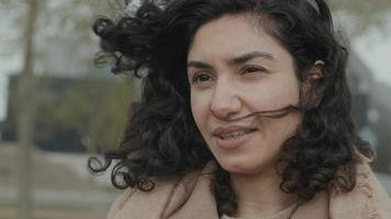 vrouw met haar dat in de wind waait praat video