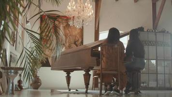 Girl and woman sitting at grand piano whilst talking video