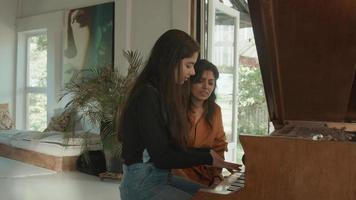Girl tries playing the piano and woman sits next to her video