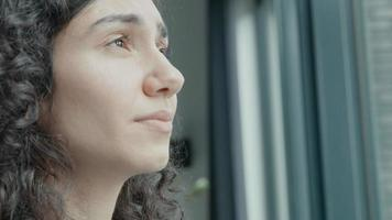 Woman looks through window with tears in her eyes video