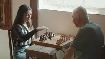 Girl explains how to play chess to man sitting at table video