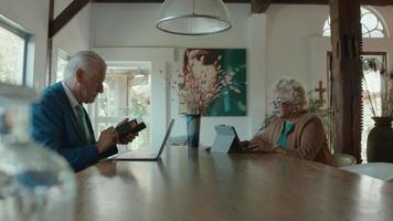 Woman and man sitting at table and both using laptops video