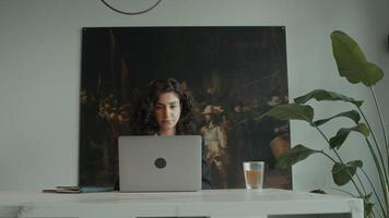 La mujer se sienta a la mesa con un portátil y responde a una llamada telefónica video