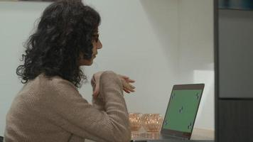 Woman at table has video call on laptop with green screen and writes