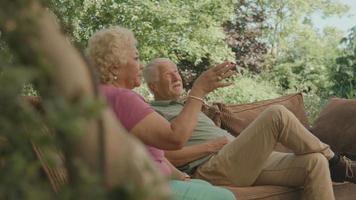 Man listens to woman sitting in garden video