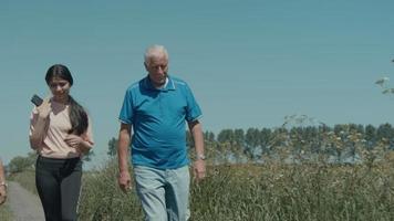 um homem uma menina e uma mulher caminhando e conversando no campo video