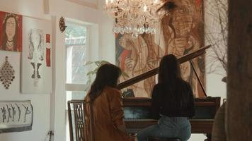 Girl and woman sitting at grand piano whilst playing video