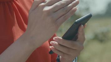 mains de femme dans la zone verte en tapant sur smartphone video