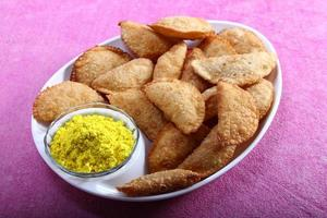 Gujia in plate with holi color in bowl photo