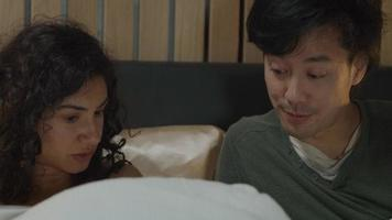 Woman and man reading and talking together whilst lying in bed video