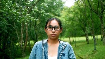 portrait d'une femme à lunettes regardant la caméra avec un visage souriant debout au milieu de la nature dans le jardin de printemps. concepts de voyage et de bonheur. video