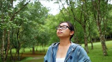 Portrait of a woman in glasses enjoying with nature standing in the spring garden. Travel and happiness concepts. video
