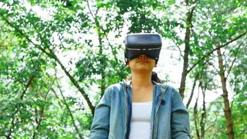 Happy woman wearing VR-headset glasses of virtual reality in forest and enjoying the nature on a sunny summer day in spring garden. Modern technology concept. video