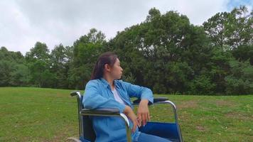 Cheerful disabled woman in a wheelchair enjoying the nature on a sunny summer day in spring garden. video